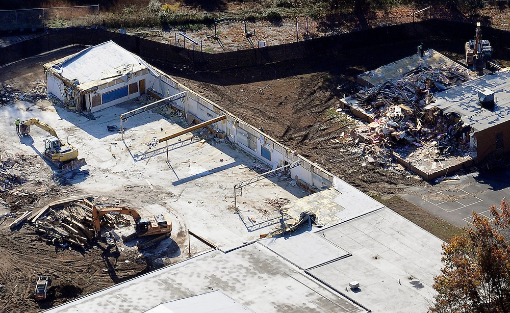 A backhoe digs through the rubble as the demolition of Sandy Hook Elementary School continues,  Monday, Oct. 28, 2013, in Newtown, Conn.  Workers have begun demolishing the building where a gunman killed 20 children and six adults. The project will take several weeks. Newtown has accepted a $50 million state grant to raze the building and build a new school, expected to open by December 2016. (AP Photo/Jessica Hill)