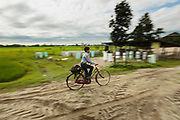 A schoolboy cycles past the biosand filter factory on his way to school in Sharanamati. The factory can be reached via a sandy road. It requires no electricity and no more than a light shelter to provide workers with some protection from the elements.