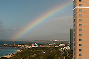 A rainbow can be seen reaching the Waianae Mountains in the distance in Hawaii.
