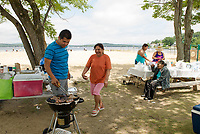 Omar Garcia and Ana Gonzelas cook up some steaks and spanish rice at Endicott Rock Park on Weirs Beach with family visiting from Chelsea, MA and Brooklyn, NY on Saturday.   (Karen Bobotas/for the Laconia Daily Sun)
