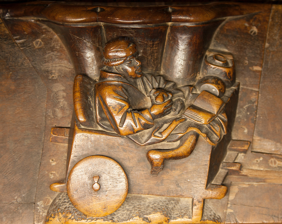 Misericordia: man riding in a wheelbarrow - like cart.  He holds a dog (?) and looks at an open book and seems quite comfortable.