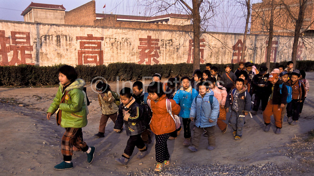 Young primary school children (8 year olds), finish lessons mid afternoon and walk out of Dong Da Jian village Elementary school, Saahxi province and head back home to do their homework and have dinner, China