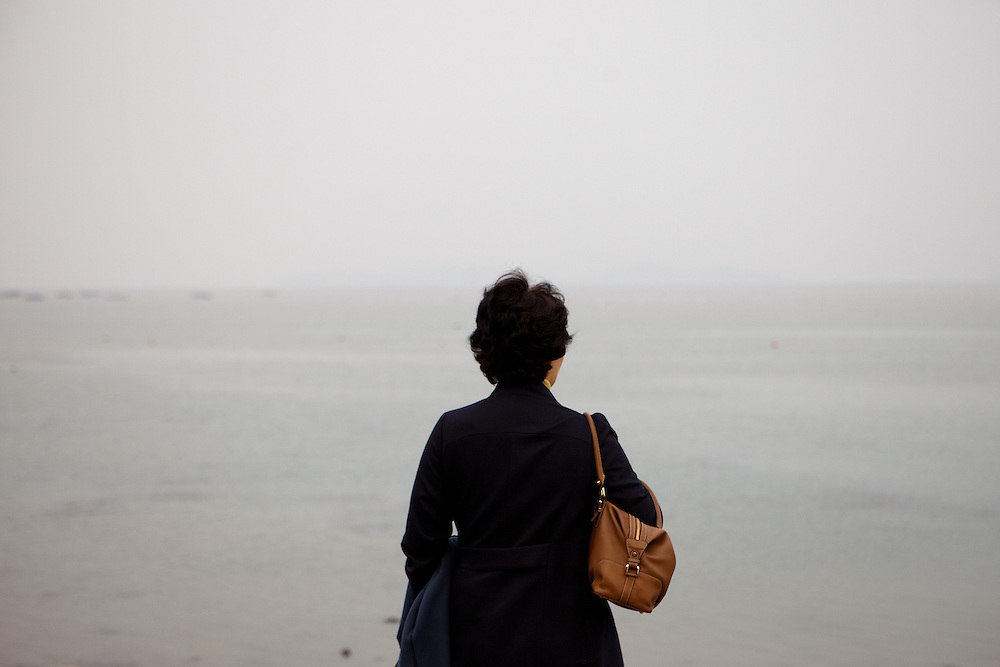 """Woman watching the already closed  """"Mysterious Sea Road"""" at Hoedong shore (Jindo island) which is usually for about one and a half hour fully open. Jindo is the 3rd biggest island in South Korea located in the South-West end of the country and famous for the """"Mysterious Sea Route"""" or """"Moses Miracle"""" . Every spring thousands flock to the shores of Jindo to walk the mysterious route that stretches roughly three kilometers from Hoedong to the distant island of Modo. Materializing from the rise and fall of the tides, the divide can reach as wide as forty meters."""