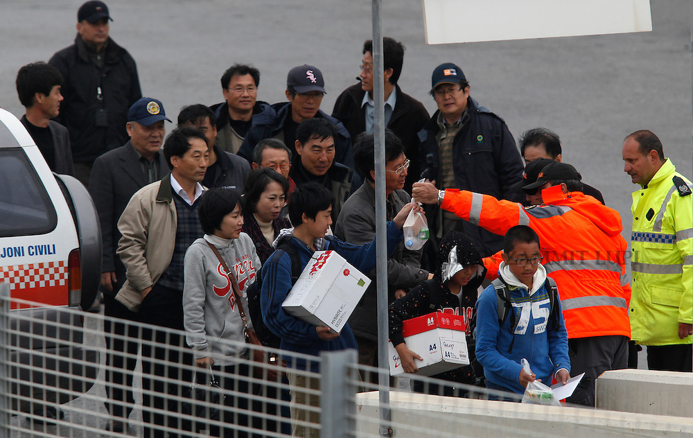South Korean nationals are given food and water after arriving on the South Korean Navy destroyer Choi Young in Valletta's Grand Harbour March 4, 2011.  The ship evacuated 32 South Koreans from Tripoli, according to an embassy official.  Over 14,000 people have been evacuated from Libya to Malta since the crisis broke out, according to local officials..REUTERS/Darrin Zammit Lupi (MALTA)