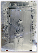 eroding glass plate with a young adult man sitting in front of door