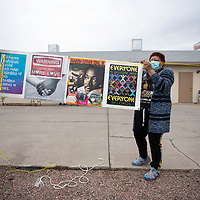 Mona Fraiser hangs a banner in front of St. Paul Missionary Baptist Church Monday as they start their food drive benefiting the Community Pantry in Gallup. Fraiser organized the food drive in honor of Dr. Martin Luther King Jr. day in place of their annual celebration due to COVID-19 restrictions.