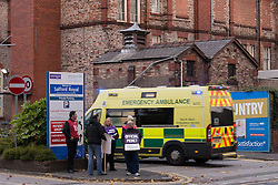 """© Licensed to London News Pictures . 13/10/2014 . Salford , UK . An ambulance responding to an emergency arrives at the hospital's A&E entrance . NHS staff picket outside the Salford Royal (formerly """" Hope """") Hospital in Greater Manchester as nurses, midwives and ambulance staff stage a four hour strike over pay .  Photo credit : Joel Goodman/LNP"""