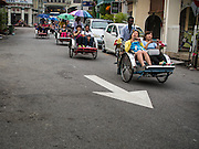07 OCTOBER 2014 - GEORGE TOWN, PENANG, MALAYSIA: Chinese tourists ride a trishaw (bicycle powered rickshaw) in George Town (also Georgetown), the capital of the state of Penang in Malaysia. Named after Britain's King George III, George Town is located on the north-east corner of Penang Island. The inner city has a population of 720,202 and the metropolitan area known as George Town Conurbation which consists of Penang Island, Seberang Prai, Kulim and Sungai Petani has a combined population of 2,292,394, making it the second largest metropolitan area in Malaysia. The inner city of George Town is a UNESCO World Heritage Site and one of the most popular international tourist destinations in Malaysia.              PHOTO BY JACK KURTZ