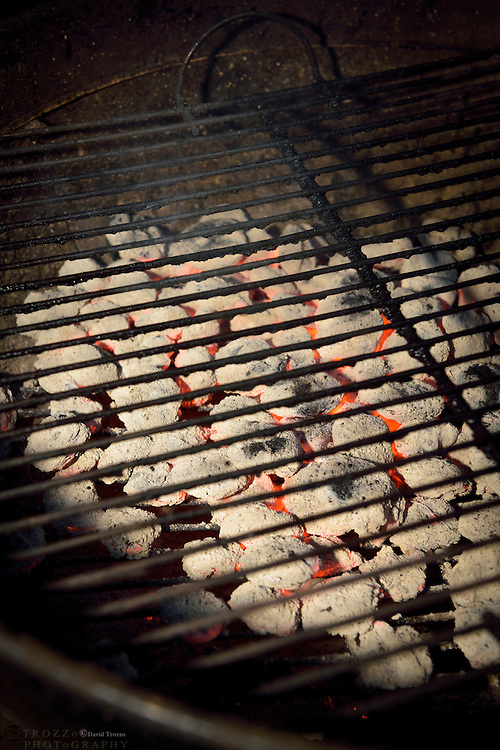 Hot empty barbecue grill with smoldering coals.