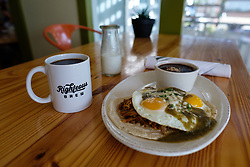 Plate of ranchero green eggs and ham and coffee at Righteous Foods, Fort Worth, Texas, USA.