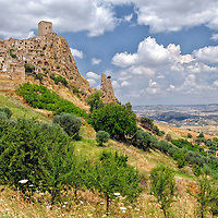 Italy. Basilicate. Craco. Picturesque view of the medieval hilltop ghost town of Craco which is dominated by its magnificent Norman period tower. Scenically rising above its mesmerizing landscape, the town overlooks the Cavone river valley in the region of Basilicate in southern Italy.