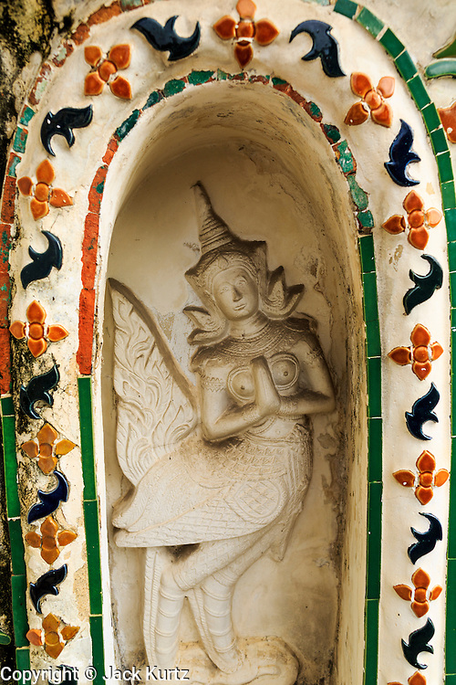 """23 SEPTEMBER 2013 - BANGKOK, THAILAND:  An angel at Wat Arun. The angel figures are scheduled to be renovated by Thai artisans during the renovation of the temple. The full name of the temple is Wat Arunratchawararam Ratchaworamahavihara. The outstanding feature of Wat Arun is its central prang (Khmer-style tower). The world-famous stupa, known locally as Phra Prang Wat Arun, will be closed for three years to undergo repairs and renovation along with other structures in the temple compound. This will be the biggest repair and renovation work on the stupa in the last 14 years. In the past, even while large-scale work was being done, the stupa used to remain open to tourists. It may be named """"Temple of the Dawn"""" because the first light of morning reflects off the surface of the temple with a pearly iridescence. The height is reported by different sources as between 66,80 meters and 86 meters. The corners are marked by 4 smaller satellite prangs. The temple was built in the days of Thailand's ancient capital of Ayutthaya and originally known as Wat Makok (The Olive Temple). King Rama IV gave the temple the present name Wat Arunratchawararam. Wat Arun officially ordained its first westerner, an American, in 2005. The central prang symbolizes Mount Meru of the Indian cosmology. The temple's distinctive silhouette is the logo of the Tourism Authority of Thailand.          PHOTO BY JACK KURTZ"""