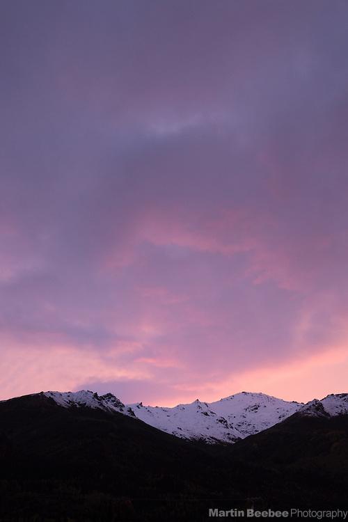 Twilight alpenglow on clouds above mountain ridge, Denali National Park, Alaska