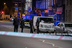 © Licensed to London News Pictures. 10/04/2021. London, UK. Police officer's stand at the crime scene after a 17-year-old boy was fatally stabbed in Sydenham. Police were called to Hazel Grove, junction with Sydenham Road, at 19:19BST on Saturday, 10 April after reports of a male lying injured on the ground. Officers attended with medics from the London Ambulance Service and the London Air Ambulance. They found a 17-year-old male who had been stabbed. Despite the best efforts of the emergency services, he was pronounced dead shortly after 20:00hrs. His next of kin have been informed. Photo credit: Peter Manning/LNP