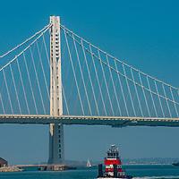 A tug boat motors past under the eastern span of the San Francisco Bay Bridge, California.