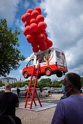 © Licensed to London News Pictures. 14/07/2021. LONDON, UK.  Passers by on the South Bank view an ice cream van appearing to be carried aloft by red balloons.  The stunt by Virgin Red is promoting a new loyalty programme for customers to coincide with the UK coming out of lockdown on 19 July.  Photo credit: Stephen Chung/LNP