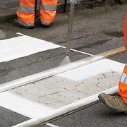 Laborers spray painting zebra crossing on road