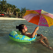 Young children enjoy the pristine waters of White Beach with umbrella's to protect themselves from the sun on Boracay Island, the Philippines on October 3, 2008. Photo Tim Clayton..Asian tourists at White Beach, Boracay Island, the Philippines...The 4 km stretch of White beach on Boracay Island, the Philippines has been honoured as the best leisure destination in Asia beating popular destinations such as Bali in Indonesia and Sanya in China in a recent survey conducted by an International Travel Magazine with 2.2 million viewers taking part in the online poll...Last year, close to 600,000 visitors visited Boracay with South Korea providing 128,909 visitors followed by Japan, 35,294, USA, 13,362 and China 12,720...A popular destination for South Korean divers and honeymooners, Boracay is now attracting crowds of tourists from mainland China who are arriving in ever increasing numbers. In Asia, China has already overtaken Japan to become the largest source of outland travelers...Boracay's main attraction is 4 km of pristine powder fine white sand and the crystal clear azure water making it a popular destination for Scuba diving with nearly 20 dive centers along White beach. The stretch of shady palm trees separate the beach from the line of hotels, restaurants, bars and cafes. It's pulsating nightlife with the friendly locals make it increasingly popular with the asian tourists...The Boracay sailing boats provide endless tourist entertainment, particularly during the amazing sunsets when the silhouetted sails provide picture postcard scenes along the shoreline...Boracay Island is situated an hours flight from Manila and it's close proximity to South Korea, China, Taiwan and Japan means it is a growing destination for Asian tourists... By 2010, the island of Boracay expects to have 1,000,000 visitors.
