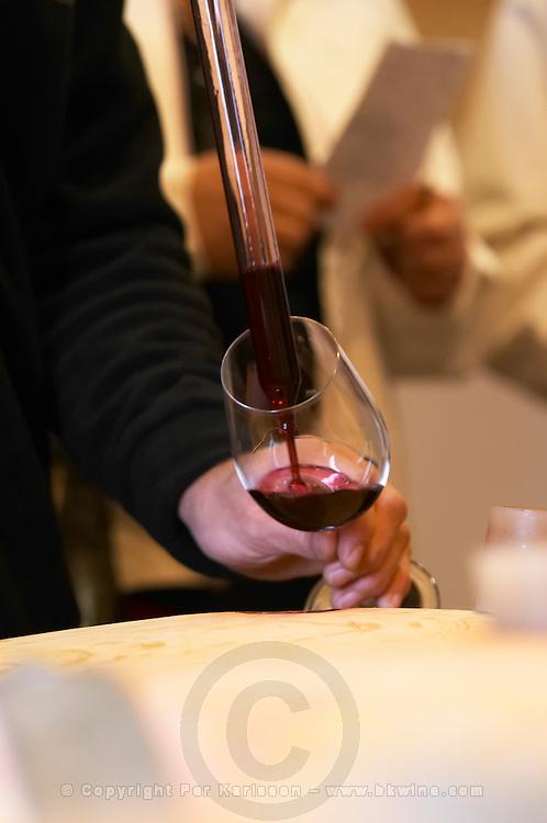 sampling wine with a pipette from a barrel ch gd barrail lamarzelle figeac saint emilion bordeaux france