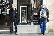 """March, 19th, 2020 - Paris, Ile-de-France, France: Rue Turenne, residents with masks and shop window, Paris, on the third day of a near total lockdown imposed in France. All journeys outside the home unless justified for essential professional or health reasons are outlawed. Anyone flouting the new regulations is punished with monetary fines. French police control of citizens and inspection of valid papers allowing citizens to travel. The most extreme measures so far in France to control the spread of the Coronavirus. Earlier in the week, President of France, Emmanuel Macron, said that citizens must stay at home from midday on Tuesday for at least 15 days. He said """"We are at war, a public health war, certainly but we are at war, against an invisible and elusive enemy"""". Nigel Dickinson"""