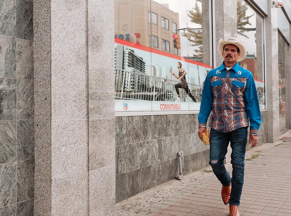 Street candid of man in cowboy attire walking on street. West New York, NJ