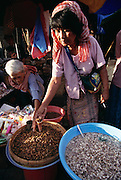 A saleswoman at the middle market in Phnom Penh, Cambodia measures silkworm pupae. She also sells bee larvae (in blue tub). Image from the book project Man Eating Bugs: The Art and Science of Eating Insects.
