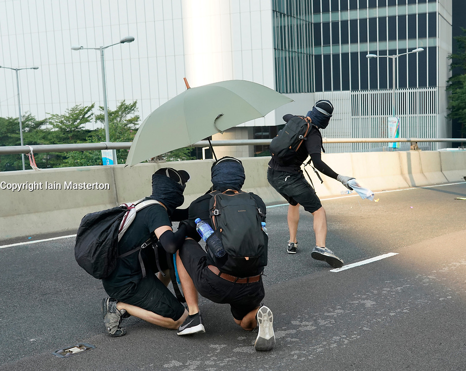 Hong Kong. 1 October 2019. After a peaceful march through Hong Kong Island by an estimated 100,000 pro democracy supporters, violent flared up at Tamar, Admiralty and moved through Wanchai district. Police used teargas and baton rounds and water cannon. Hard core group lit fires, threw bricks and Molotov cocktails at police. Violence continues into evening. Protestor throws Molotov cocktail at police. Iain Masterton/Alamy Live News.