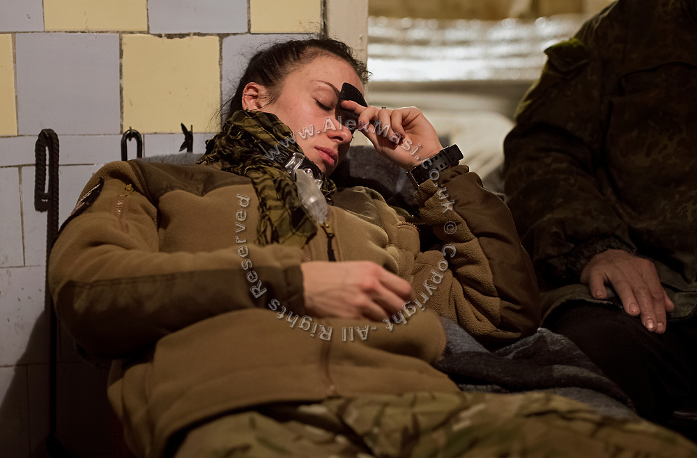 Elena Mosiychuk, (nom the guerre Maliok, or 'Baby') a member of ASAP, is taking a moment of calm while talking about her brother, who died in the war, as she seats in an improvised 'warehouse' for medicines, set up in an abandoned home in the village of Klynove, near the frontline in eastern Ukraine.