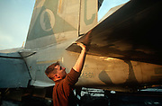 A US Navy crewman cleans the underside of flight-critical surfaces on the deck of US Navy aircraft carrier USS Harry S Truman during its deployment patrol of the no-fly zone at an unknown location in the Persian Gulf, on 8th May 2000, in the Persian Gulf. The Truman is the largest and newest of the US Navys fleet of new generation carriers, a 97,000 ton floating city with a crew of 5,137, 650 are women.