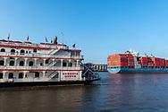 Savannah, Georgia - July 29, 2021: The container ship Mukaddes Kalkavan, departing Savannah for Alexandria, Egypt, passes the tourist river boat Georgia Queen on the Savannah River.