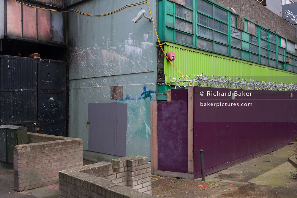 An urban landscape of CCTV camera, security fencing and a palette of colour at the back of a tower block on the Aylesbury Estate, on 4th January, London borough of Southwark, England.