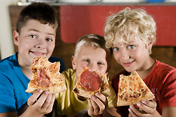 Three boys holding slices of pizza