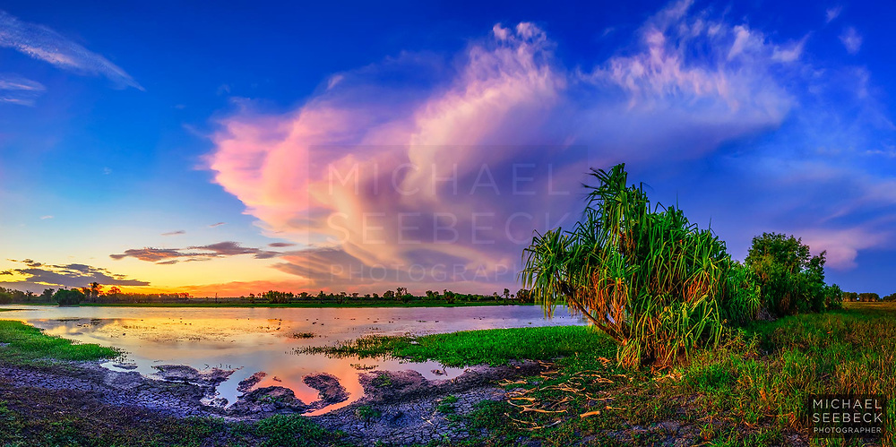 A dissipating thunderstorm at sunset is reflected in the aters of the South Alligator River in the Northern Territory. Crocodile slides are small channels created in the mud by the sliding of crocodiles, and can be seen at the bottom left of the photograph.<br /> <br /> Limited Edition Print; Edition of 125.<br /> <br /> 'Image Size' below refers to the size of the thumbnail. This is a high resolution large format photograph.