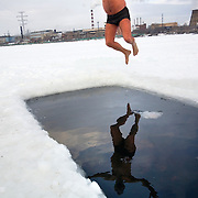 A Russian ice-swimmer jumps into a frozen lake in Yekaterinburg, capital of Russia's central Ural region on the edge of Siberia. The temperature was around -10 degrees celcius.