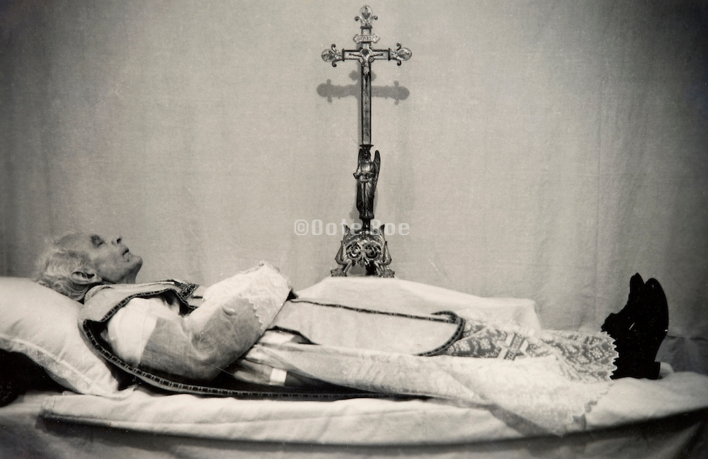 vintage photo of a priest laying on his dead bed