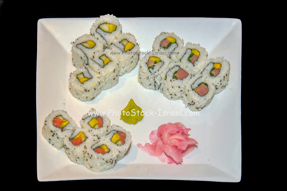 A plate of sushi at a Japanese restaurant on black background