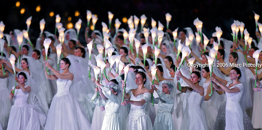 """Brides, 398 of them to be exact, hold up flowers that act as lamps in the """"River of Light"""" sequence duirng the Closing Ceremony for the 2006 Winter Olympics Sunday February 26, 2005 at the Stadio Olimpico in Turin, Italy. The Closing Ceremony featured a dizzying array of circus acts, parades and a general carnival atmosphere. Performers included clowns swivelling in large hoops, ballerinas and tumblers, acrobats dangling high above the stage from ribbons and rings, a stilt walker jumping rope, dancers dressed as Tarot cards and highflying acrobats performing over a tunnel of wind. The Closing Ceremony capped off 16 days of Olympic competition that saw the U.S. win 25 total medals, second to only Germany with 29 total medals..(Photo by Marc Piscotty/ © 2006)"""