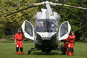 MD902 Explorer helicopter crew from the Kent, Surrey & Sussex Air Ambulance Trust on the ground in Ruskin Park after emergency flight to Kings College Hospital in south London. The medical flight crew are amused at something funny elsewhere in this public space, waiting to lift off again for another emergency case. The Air Ambulance (KSSAAT) fly state of the art Helicopter Emergency Medical Service (HEMS) aircraft operating 365 days a year, out of their base at Marden in Kent and Redhill in Surrey. They're capable of delivering our crews anywhere in our region in under 20 minutes flying time, attending over 20,000 missions