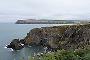 Views out to sea and coastline of high jagged rocks and cliffs from the coastal path on 17th August 2021 in Newport, Pembrokeshire, Wales, United Kingdom. Newport is a town, parish, community, electoral ward and ancient port of Parrog, on the Pembrokeshire coast in West Wales at the mouth of the River Nevern in the Pembrokeshire Coast National Park.