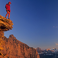 A hiker overlooks peaks of the Continental Divide in Montana's Glacier National Park.  Immediately behind him is The Garden Wall and Logan Pass. He is standing on the slopes of Mount Gould, high above the Highline Trail.