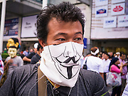 """09 JUNE 2013 - BANGKOK, THAILAND:  A member with a Guy Fawkes mask at an anti-government protest on the plaza in front of Central World in Bangkok. The White Mask protesters wear the Guy Fawkes mask popularized by the movie """"V for Vendetta"""" and the protest groups Anonymous and Occupy. Several hundred members of the White Mask movement gathered on the plaza in front of Central World, a large shopping complex at the Ratchaprasong Intersection in Bangkok, to protest against the government of Thai Prime Minister Yingluck Shinawatra. They say that her government is corrupt and is a """"puppet"""" of ousted (and exiled) former PM Thaksin Shinawatra. Thaksin is Yingluck's brother. She was elected in 2011 when her brother endorsed her.    PHOTO BY JACK KURTZ"""