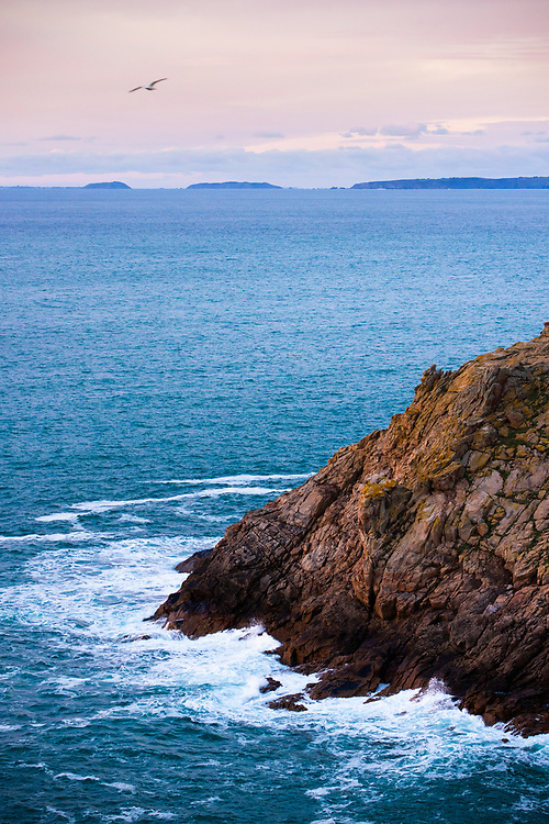 Views out to sea across the rocks and cliffs of Jersey's coastline, towards Herm and Sark at sunset in the Channel Islands
