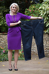 © licensed to London News Pictures. London, UK 13/11/2012. Claire Alsop, 31, from Rotherham in South Yorkshire, posing with her old jeans as she slimmed down from 21st 9lb to a 10st 1½lb. Now she's been named Slimming World's Woman of the Year 2012. Photo credit: Tolga Akmen/LNP