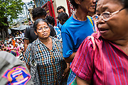 "09 AUGUST 2014 - BANGKOK, THAILAND: People line up to get into the Ruby Goddess Shrine in the Dusit section of Bangkok. The seventh month of the Chinese Lunar calendar is called ""Ghost Month"" during which ghosts and spirits, including those of the deceased ancestors, come out from the lower realm. It is common for Chinese people to make merit during the month by burning ""hell money"" and presenting food to the ghosts. At Chinese temples in Thailand, it is also customary to give food to the poorer people in the community.        PHOTO BY JACK KURTZ"