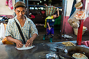 17 JUNE 2013 - YANGON, MYANMAR:  A roti vendor makes an order for a customer in a large Yangon fish market. The market serves both domestic retail customers and wholesale international customers. With thousands of miles of riverine waterways and ocean coastline Myanmar has a large seafood and fishing industry.     PHOTO BY JACK KURTZ
