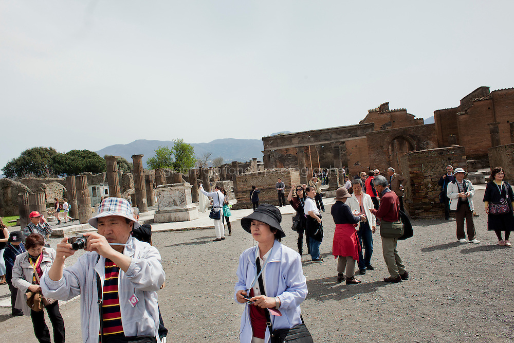 POMPEII, ITALY - 4 APRIL 2013:   Tourists visit and photograph the Forum, the city's main square, dating the 2nd century BC, in Pompeii, Italy, on April 4th, 2013. Located at the intersection between the two main streets of the original urban center, the Forum was the city's main square, surrounded on all sides by religious, political, and business buildings.<br /> <br /> In recent years, a series of collapses at the site have alarmed conservationists, who warn that the ancient Roman city is dangerously exposed to the elements ? and poorly served by the red tape, lack of strategic planning and limited personnel of the site's historically troubled management. <br /> <br /> Pompeii, along with Herculaneum, was buried under 4 to 6 meters (13 to 20 ft) of ash and pumice in the eruption of Mount Vesuvius in 79 AD. After its initial discovery in 1599, Pompeii was rediscovered as the result of intentional excavations in 1748 by the Spanish military engineer Rocque Joaquin de Alcubierre.<br /> <br /> Pompeii is an UNESCO World Heritage Site and one of the most popular tourist attractions of Italy, with approximately 2.5 million visitors every year.<br /> <br /> Gianni Cipriano for The New York Times