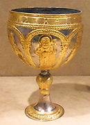 Silver gilded Chalice. In relief it shows a young Christ with halo, flanked by a deacon saint, and a youthful saint, along with the Virgin Mary with Archangels. Along the top of the chalice it has a Greek inscription.