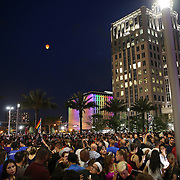 Mourners are seen as a floating lantern floats into the sky during a vigil at the Dr. Phillips Center for the Performing Arts for the victims of a mass shooting at the Pulse nightclub Monday, June 13, 2016, in Orlando, Florida.  A gunman killed dozens of people in a massacre at the crowded gay nightclub in Orlando on Sunday, making it the deadliest mass shooting in modern U.S. history. (Alex Menendez via AP)