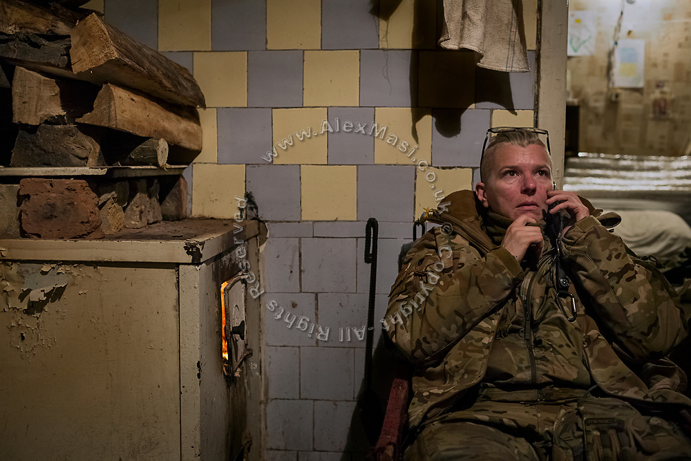 Julia Paevska is talking on the phone while sitting in an improvised 'warehouse' for medicines, set up in an abandoned home in the village of Klynove, near the frontline in eastern Ukraine.