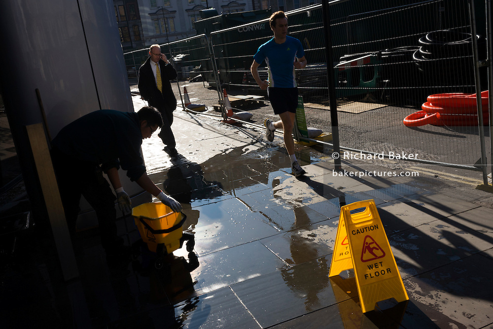 An office employee washes the pavement outside his building with water as pedestrians run and walk past.